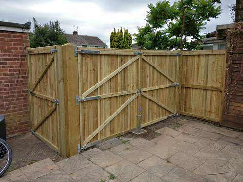 A double gate fitted between a garage and a fence, rear view.